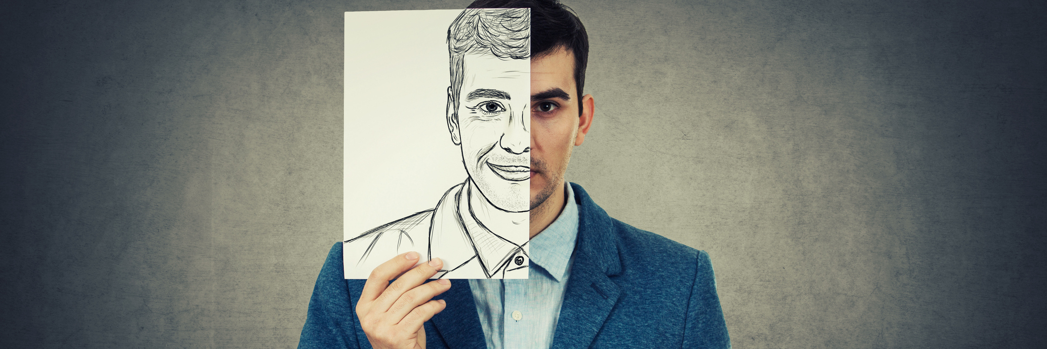 Portrait of a sad businessman hiding half his face using a white paper drawn with a fake happy emotion. Mask for hiding the real face expression.
