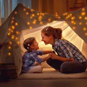 A mother and daughter under an indoor tent with lights.