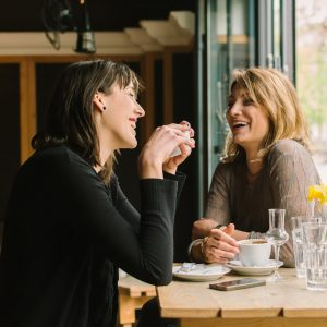 Two female friends sitting at the cafe and talking.