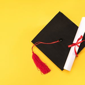 Top view of graduation mortarboard and diploma on yellow background.