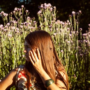 Woman in meadow looking afraid and anxious