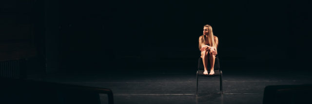 female actor alone on stage barefoot sitting on chair