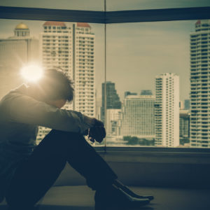 upset man in front of window with skyscrapers and lens flare