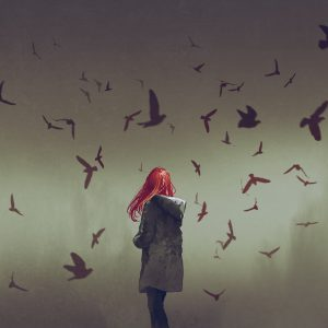 A woman standing, surrounded by birds