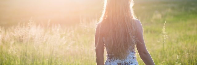 young woman walking in sunset in field