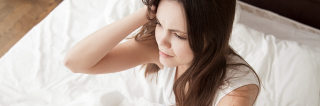 young woman sitting up in bed looking exhausted