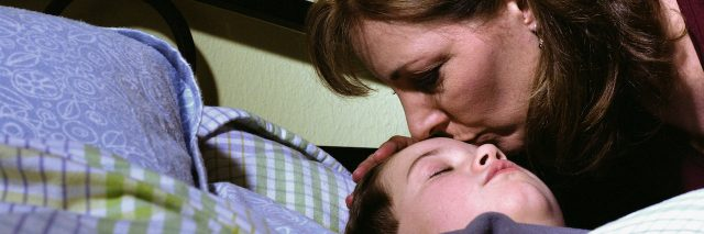 A mother kissing her child, who lies in bed