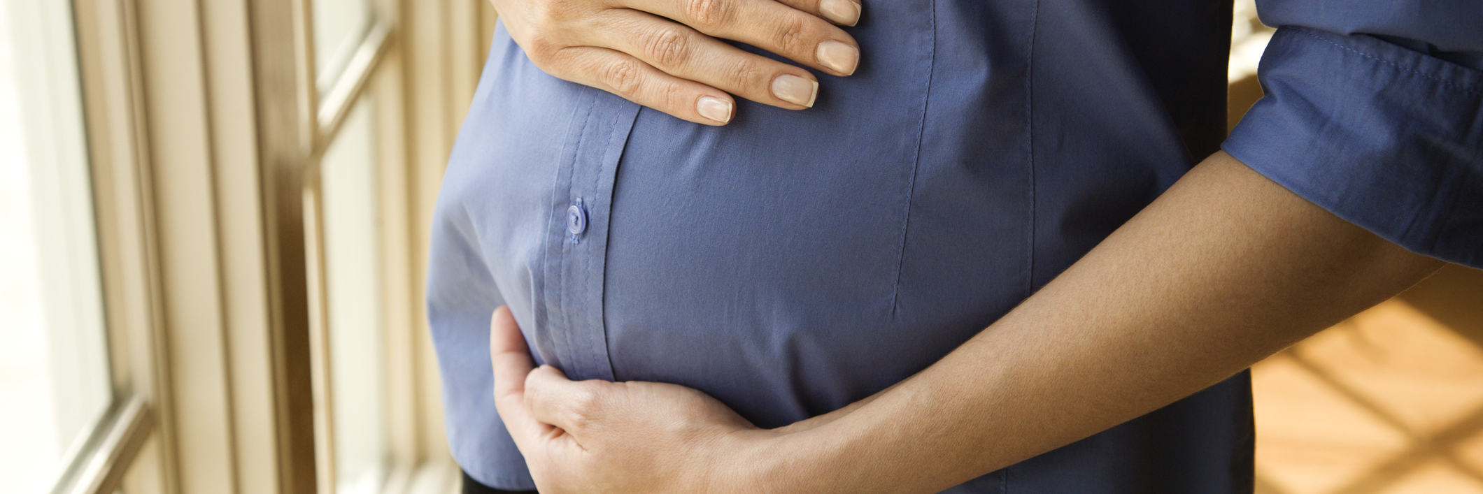 Pregnant woman wearing a denim shirt holding her belly