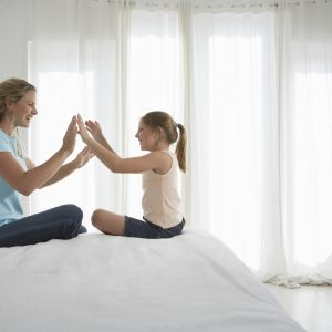 mother and daughter sitting on a bed and playing games