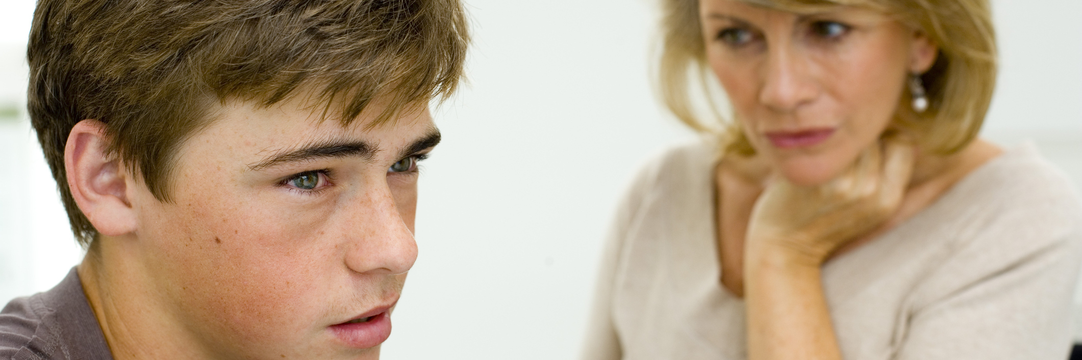 mother talking to teenage son both looking upset