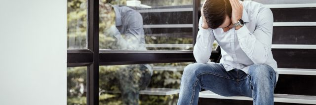 young man sitting on staircase near window holding head in despair or anxiety