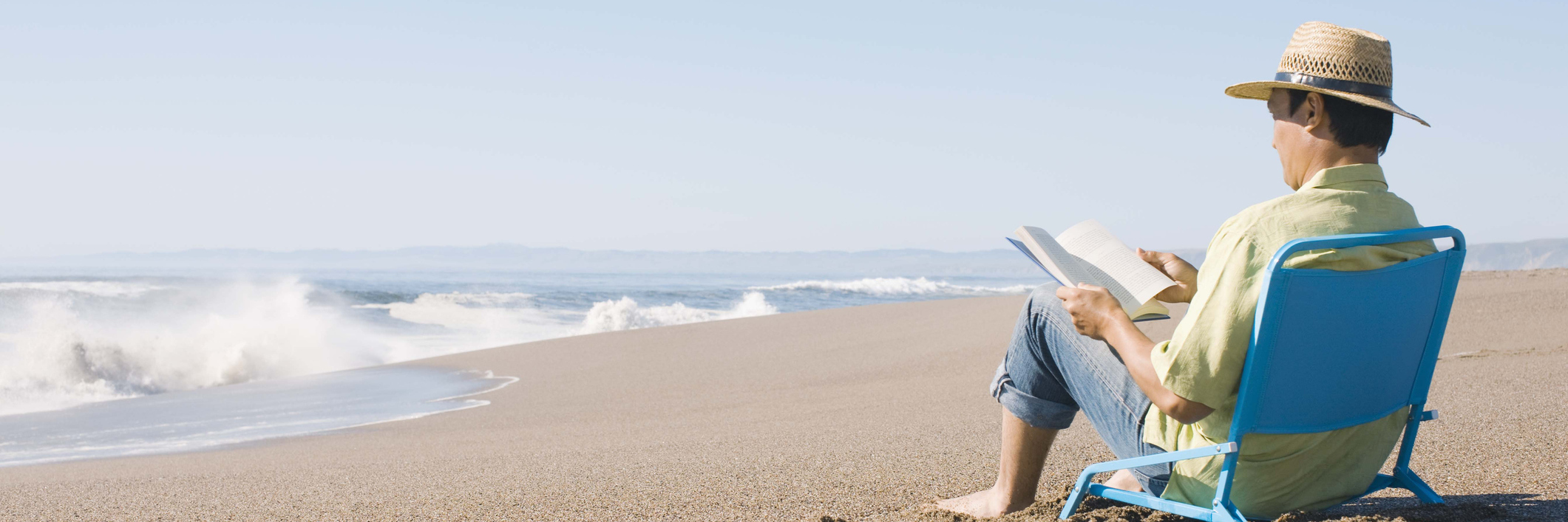 man reading a book on the beach