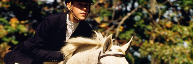 young woman on white horse jumping over obstacle