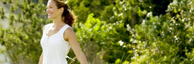 smiling woman standing in field with bare arms in white dress