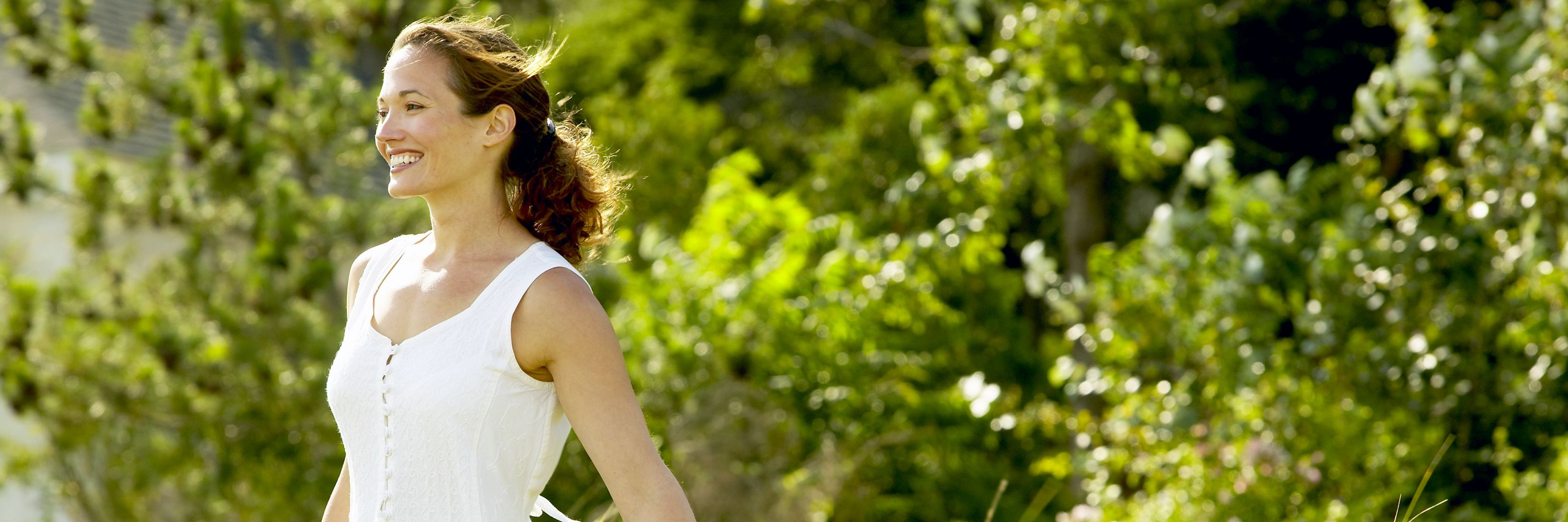 woman in white dress standing in a field and smiling