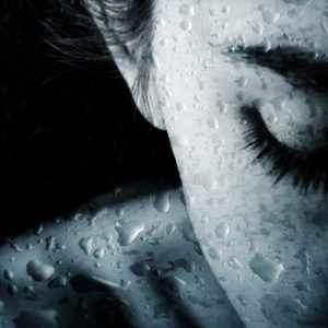 Woman with drops of rain covering her skin.
