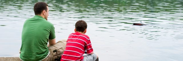 father and son sitting on pier talking by lake