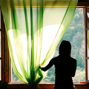 silhouette of a woman standing next to a window