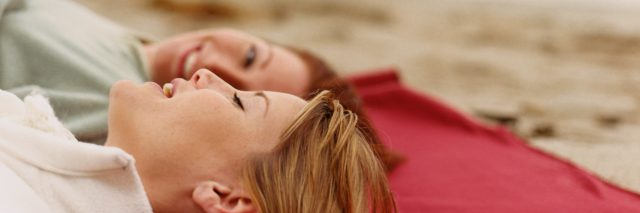 two friends lying on the beach and talking