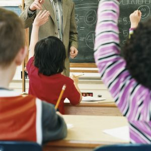 Children raising their hands in classroom during teacher's math lesson