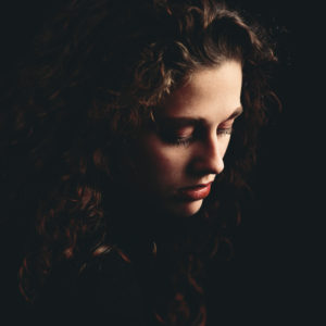 woman with brown hair in darkness looking sad