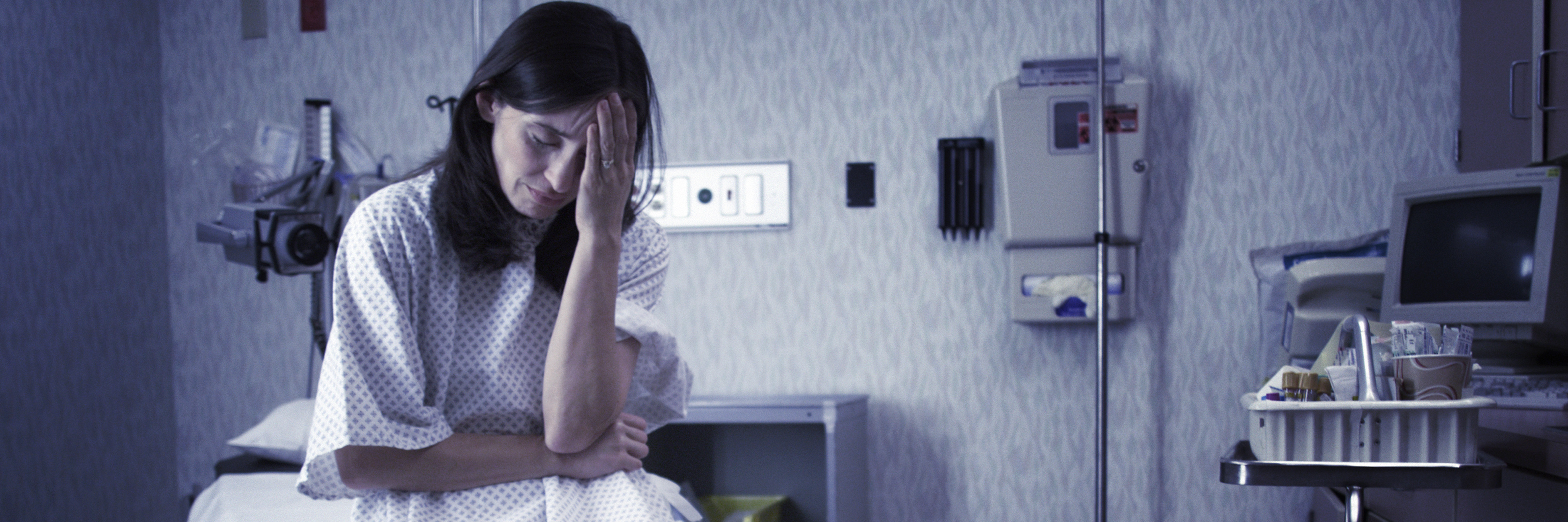 A worried patient sits in a hospital gown in a hospital room.