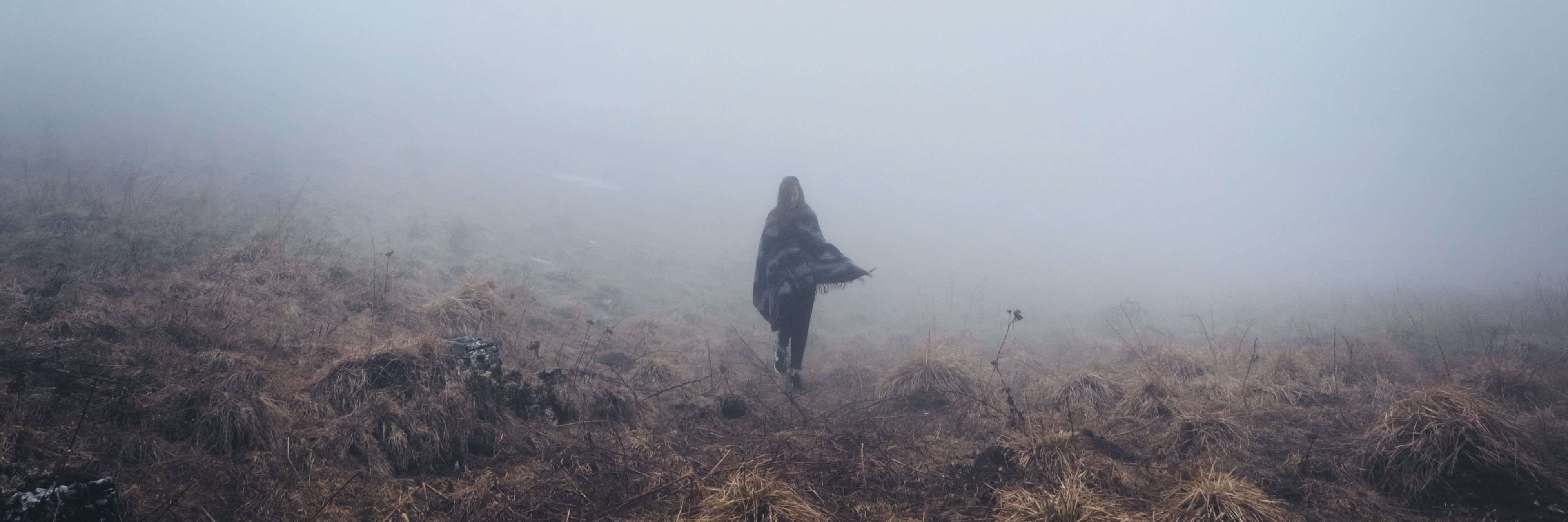 woman walking alone through fog