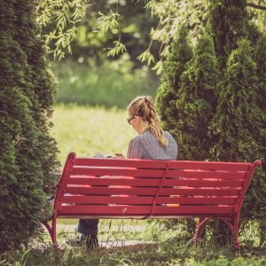 blonde woman wearing glasses reading on red bench in nature