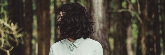 dark haired woman standing in forest with face hidden