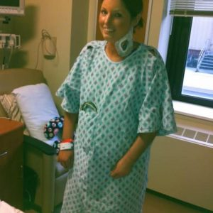 woman smiling in a hospital gown with an IV in her neck