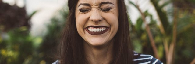 woman wearing striped top in greenhouse laughing