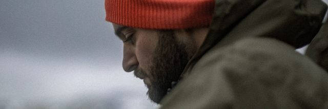 side view of man with beard and red hat looking down at ground depression