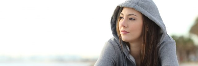 Close up of woman wearing a gray hoodie looking pensive