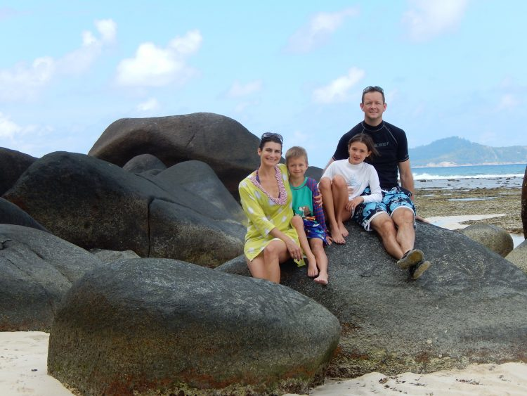 family sitting on a big rock on a beach