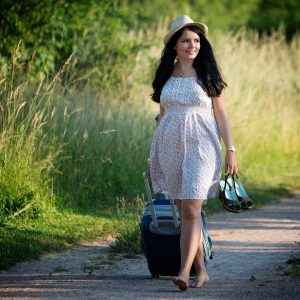 girl in summer dress walking down country lane with suitcase