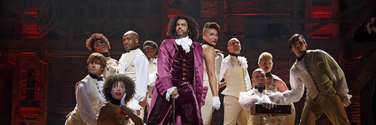 the cast of the hamilton musical stands on stage