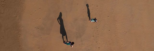 parent and child stand far apart from each other in the desert