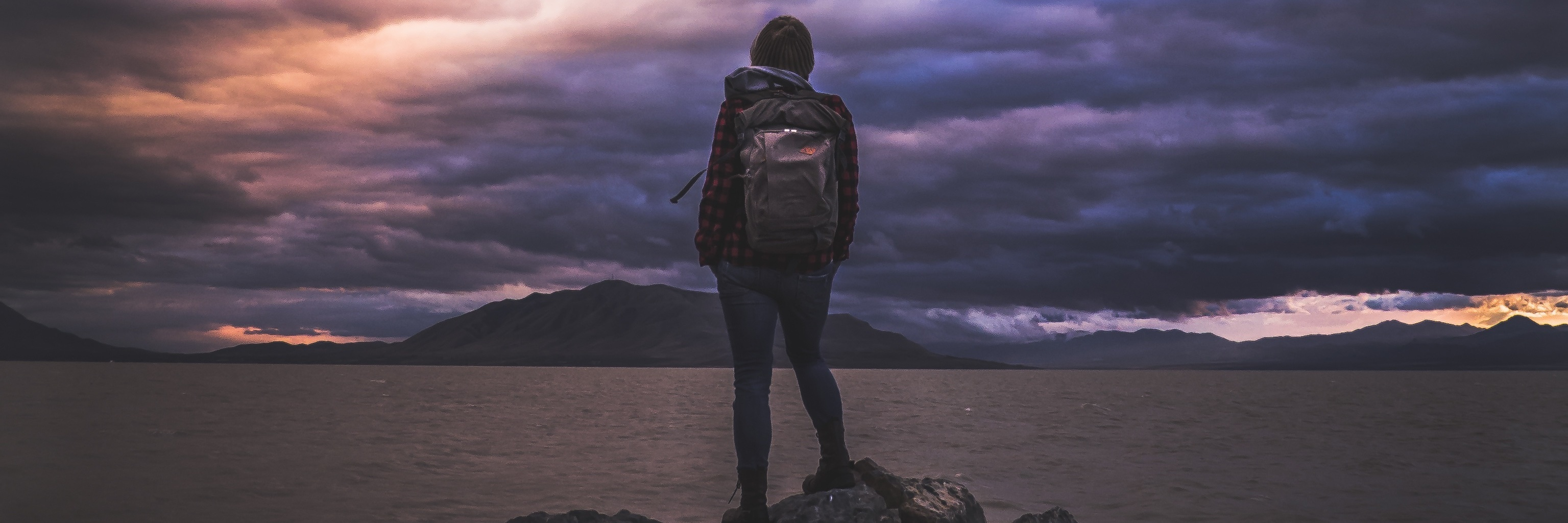 woman watching storm clouds at sunset over ocean while standing on rock