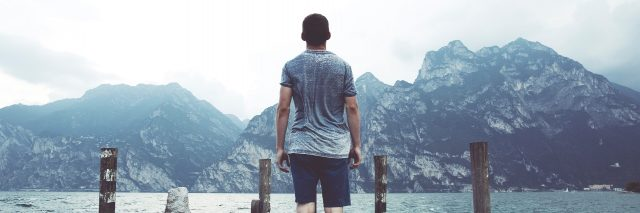 young man standing on pier looking out over water and distant mountains