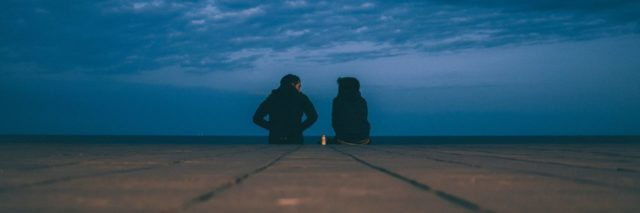 two people sitting at the end of a dock at night