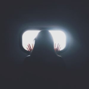 silhouette of woman against small bright window looking out with hands pressed against it