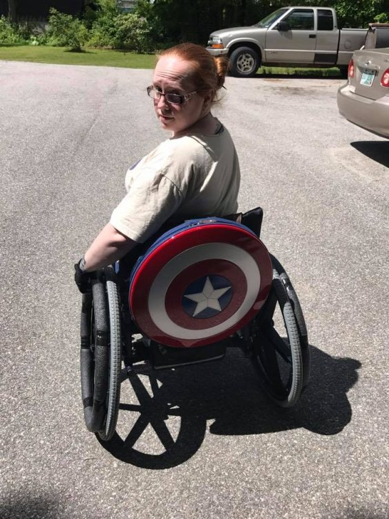 Woman sits in wheel chair, with a Captain America shield on back of her chair.