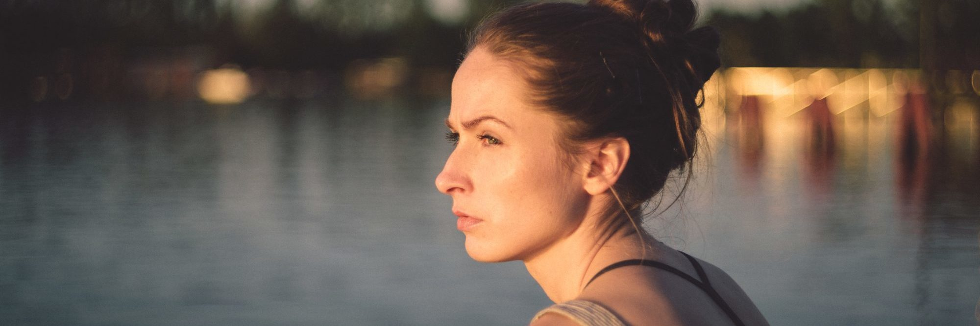 young woman in sunset by water staring out thoughtfully
