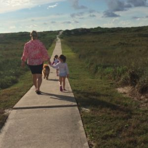 Mother holding daughter's or granddaughter's hand, walking with daughters or granddaughters down path surrounded by grass during the daytime