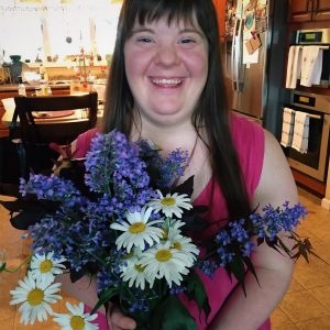 Woman with Down syndrome holdng floweres and smiling. She has brown hair and bangs.
