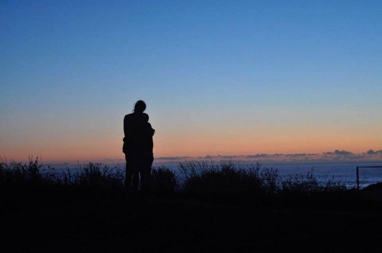 silhouette of a couple hugging in front of the ocean at dusk