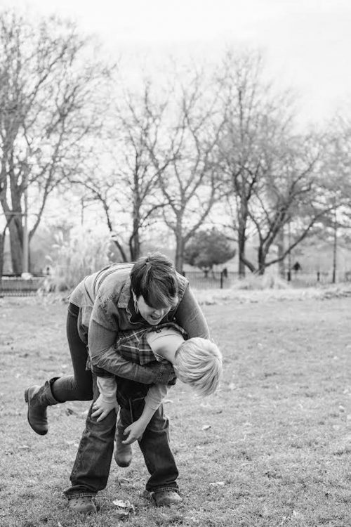 black and white photo of a woman playing outside with her son