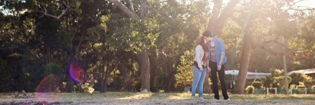 couple kissing outside in front of trees