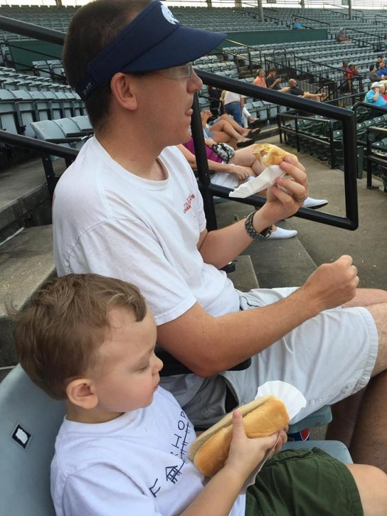 The writer's young son and husband sitting together, eating food at a sports game.