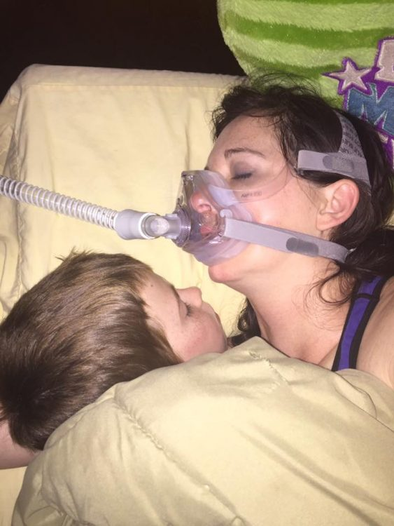 woman wearing a CPAP machine while lying in bed and cuddling with her young son